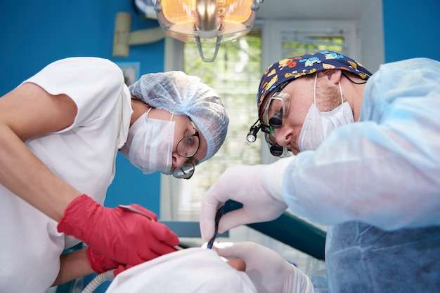 Врачи выполняют операцию в стоматологической поликлинике.