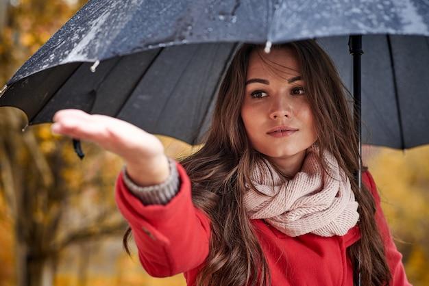 秋の公園で傘を持つ若い女性。