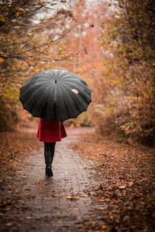 Молодая женщина с зонтиком в осенний парк.