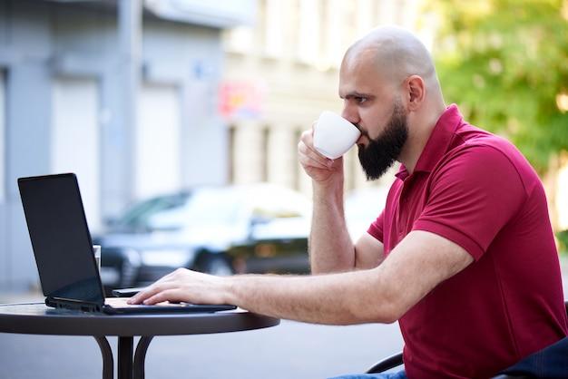 独立した若い男がカフェで働いています。