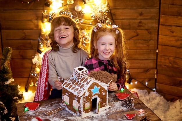 幸せな赤毛のクリスマスジンジャーブレッドとテーブルで少女。
