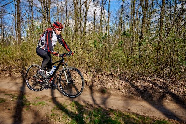 Спортсмен едет на велосипеде по бездорожью в лесу.