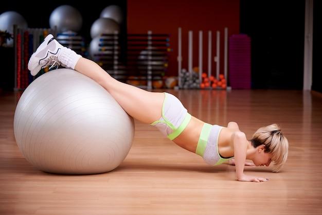 スポーツの若い女性はジムでトレーニングします。