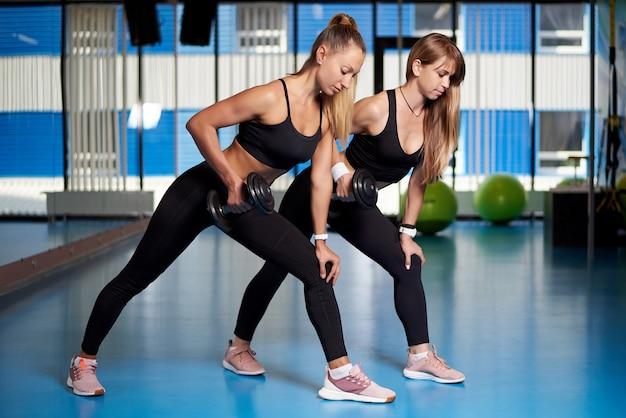 Спортивные молодые женщины занимаются в тренажерном зале.