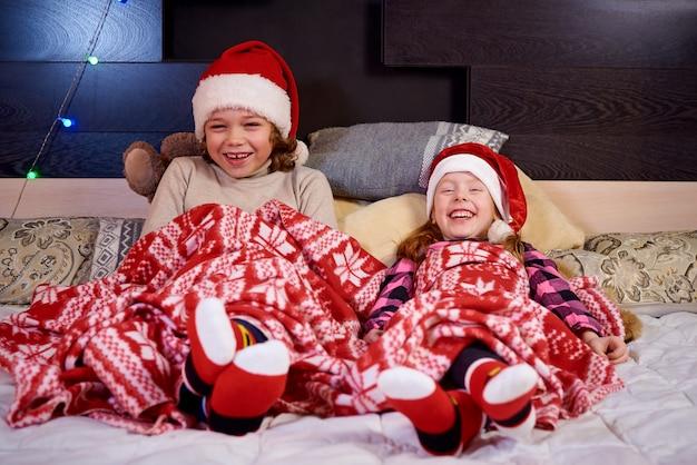 クリスマスを待っているベッドの上の幸せな女の子。