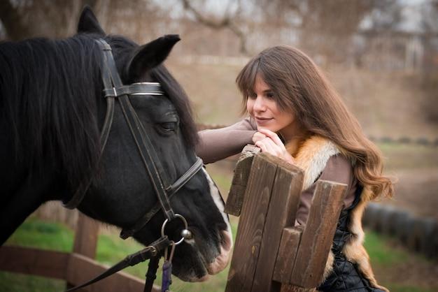 秋の曇りの日に牧場で馬と少女。