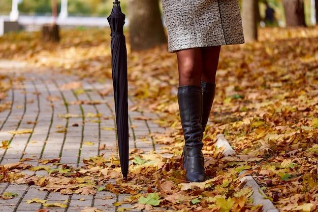 落ち葉の道に傘を持つ女性の足
