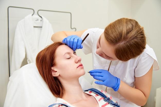 Молодая женщина на коррекцию бровей в косметологической клинике