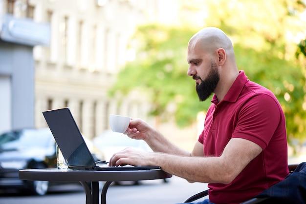 Молодой человек с ноутбуком за столом в летнем кафе