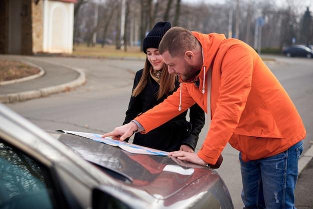 道路上の車の近くの地図を持つ若者。