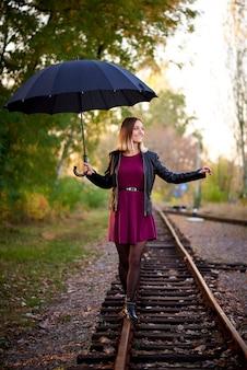 Девушка с черным зонтом идет по железной дороге.
