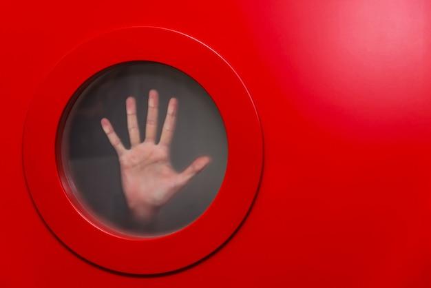 女性の手で丸い赤い舷窓
