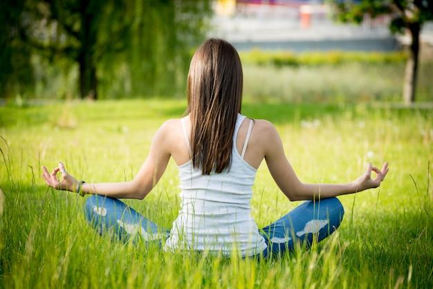 緑の芝生の上の蓮華座の女の子
