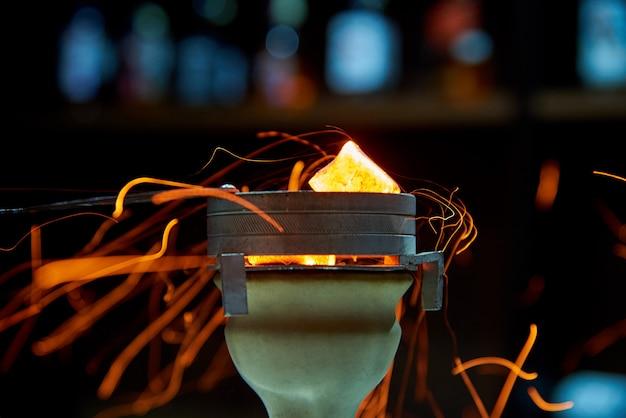 暗い背景に火花の水ギセルのボウルに石炭します。