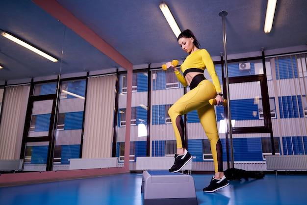 Атлетическая молодая женщина используя платформу шага в спортзале.