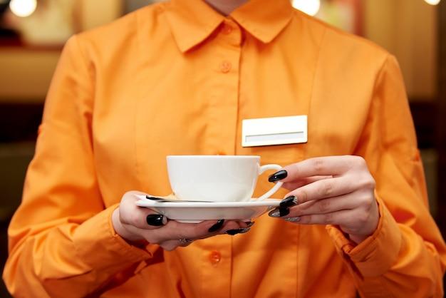 Обслуживающий персонал с чашкой кофе.
