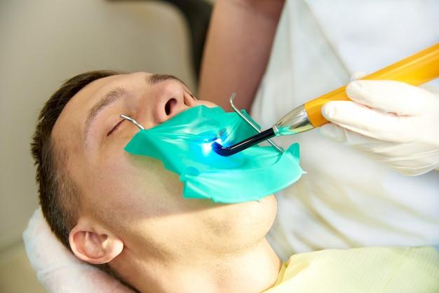 歯科用椅子に目を閉じて若い男。歯科医は歯科用重合ランプを使用します。
