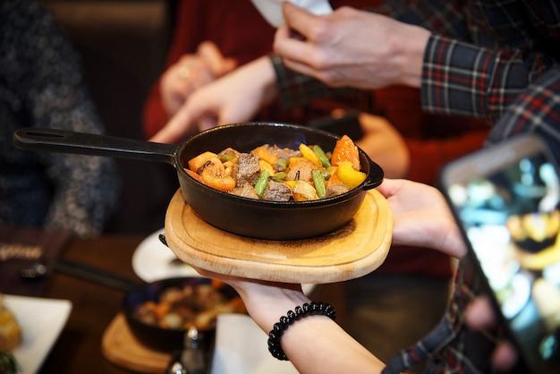 Подавать жареное мясо с овощами на сковороде в ресторане гостям.