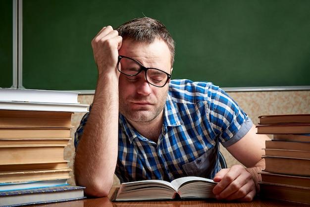 疲れて疲れ果てた学生はたくさんの本を持ってテーブルで寝ます。