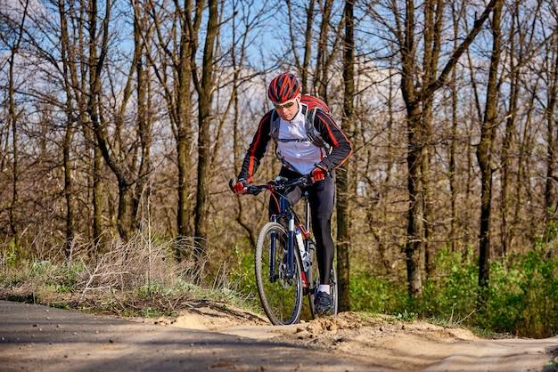 スポーツサイクリストは、春の晴れた日に森の小道を走ります。