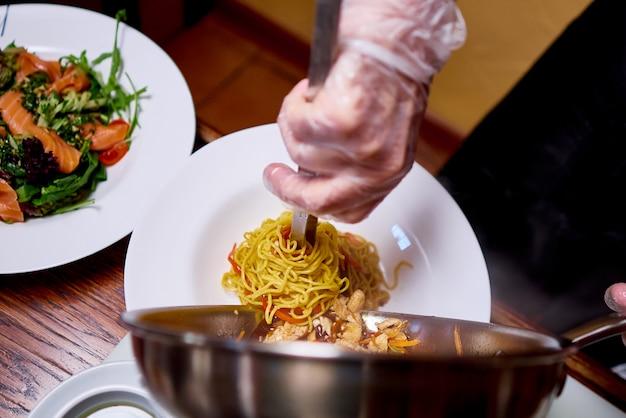 料理人がレストランのキッチンで料理を用意します。