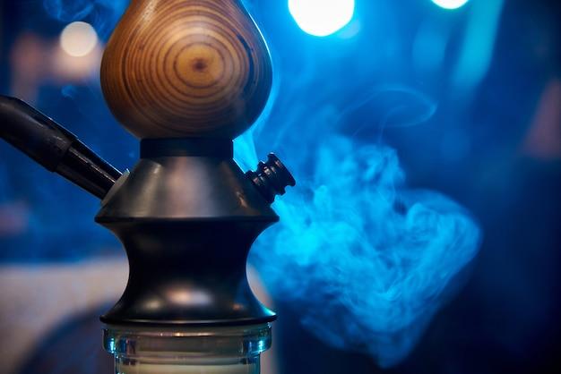 青色の背景に煙の中で水ギセルのクローズアップ