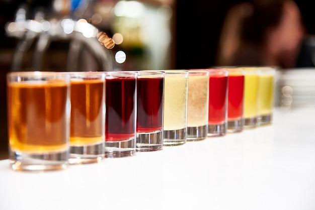 バーカウンターの色とりどりのアルコールショット