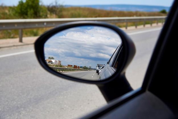 車の鏡の中の空の反射。