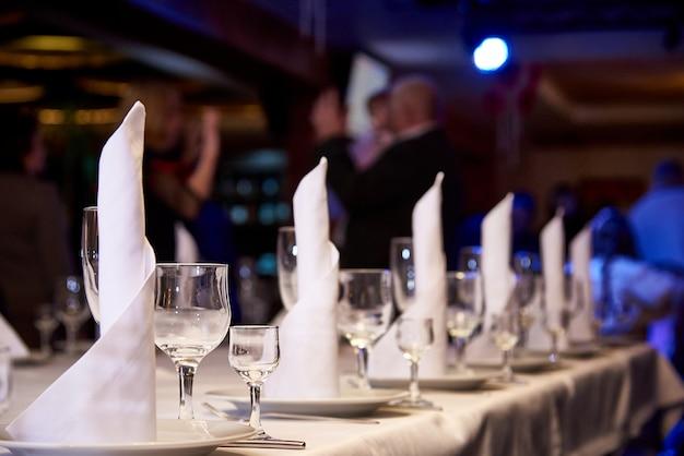 宴会テーブルの上の空のワイングラス。宴会やディナーパーティーのためのテーブルの設定。