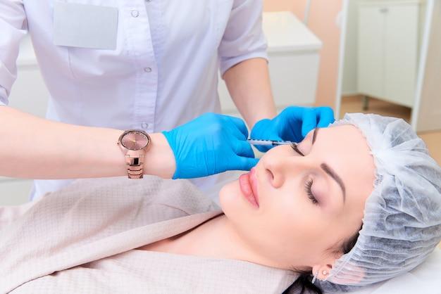 Красивая молодая женщина в клинике эстетической косметологии.