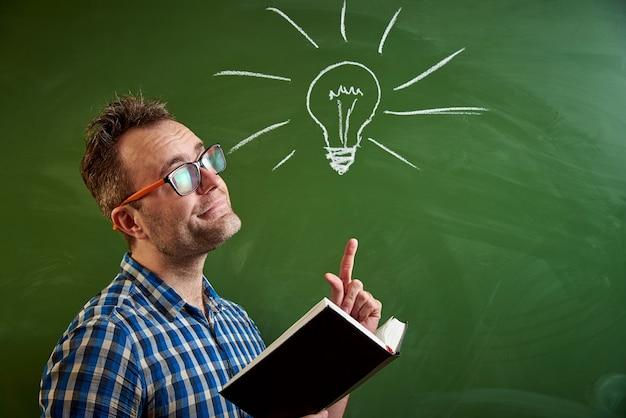 本を読んでいる若い男、アイデアはチョーク電球と黒板で思い浮かぶ。