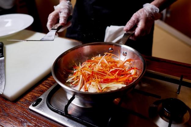 Горячая сковорода с мясом и овощами на плите. повар готовит блюдо на кухне ресторана.
