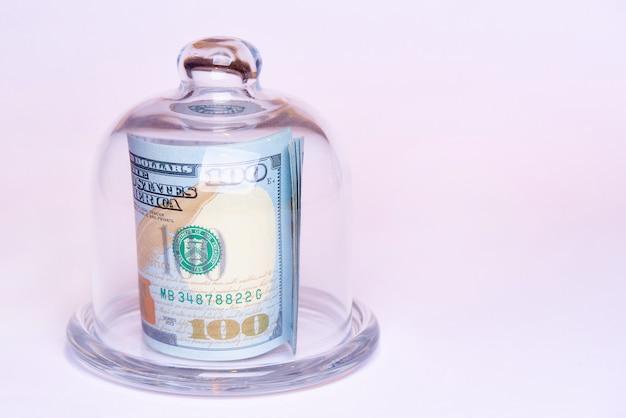白い背景の上のガラスドームの下の百ドルの価値がある紙幣。スペースをコピーします。