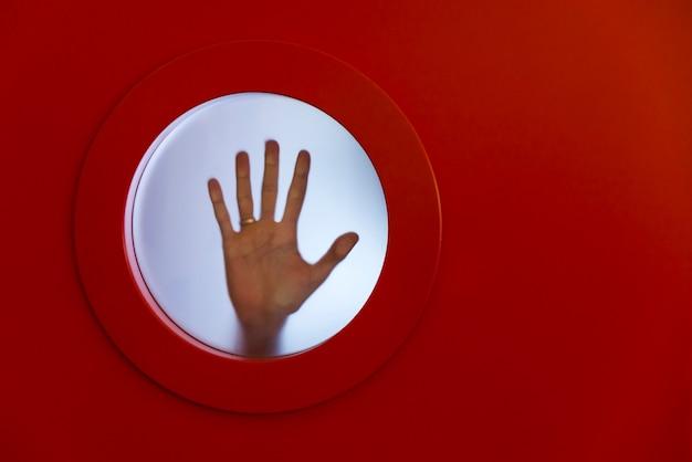 女性の手で丸い赤い舷窓。