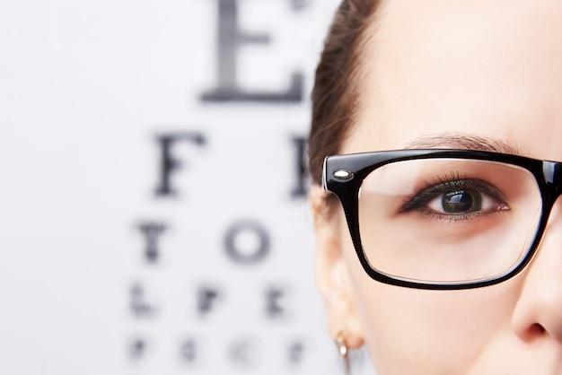 Молодая женщина в очках на фоне таблицы для зрения.