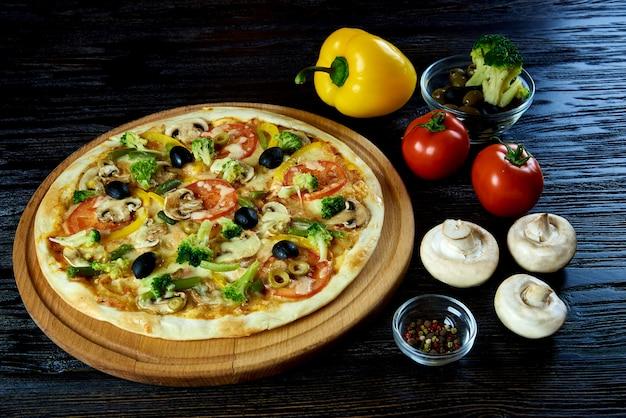 Поверхность горячей вегетарианской пиццы темная деревянная.