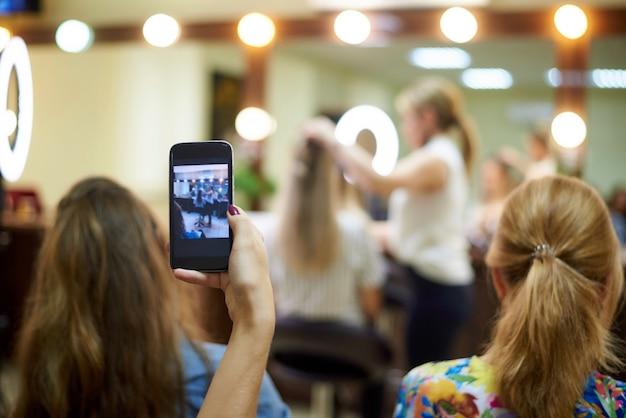 若い女性は美容室でトレーニングを撃ちます。