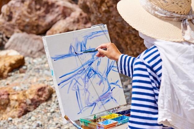 芸術家は海岸に絵を描く。