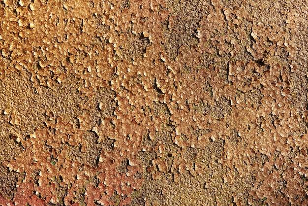 ひびの入った塗料で古いさびた金属の金色の光沢のあるキラキラテクスチャ背景。