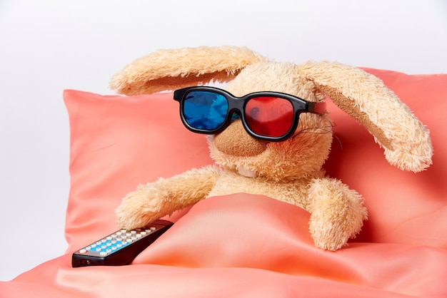 Игрушечный кролик в стереоочках с пультом от телевизора лежит в постели.