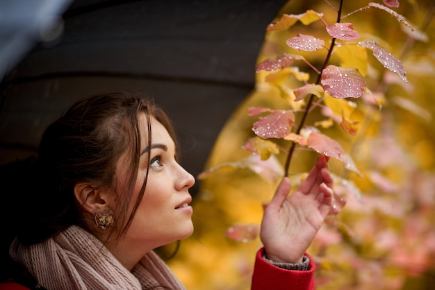 秋の公園で傘を持つ若い女。