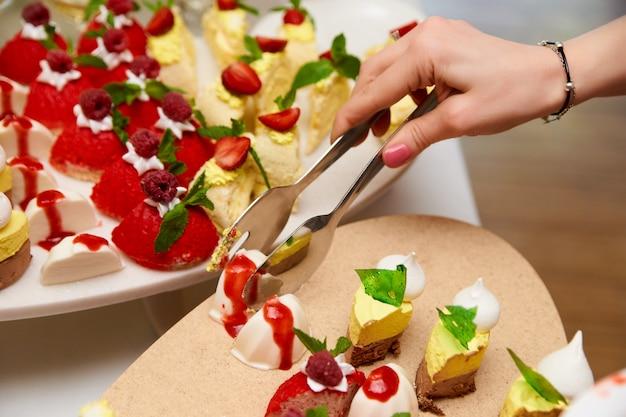 女性の手がビュッフェからケーキを取ります。