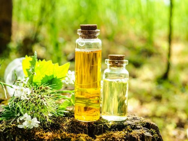 有機バイオ代替医療、漢方薬、健康なエッセンシャルオイルまたは注入のボトル、および乾燥薬草。
