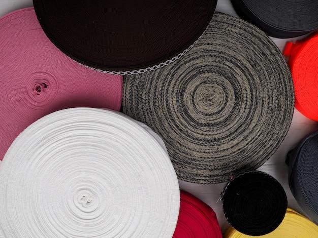 Лента разных цветов в катушках, много разноцветных катушек для текстильной промышленности