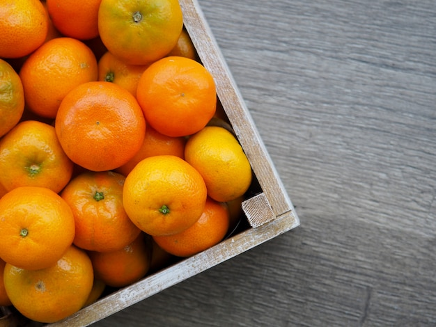 Свежие мандарины в старой коробке. на деревянном фоне.