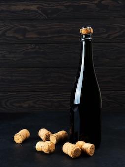 Бутылка вина на деревянный пол и гранж, рядом пробка, мишура