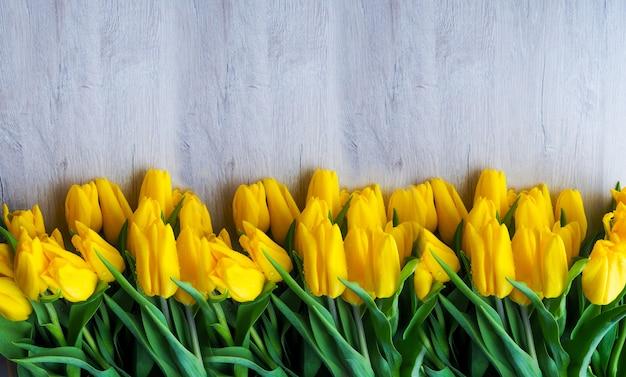 木製の背景に新鮮な黄色のチューリップ
