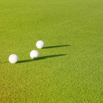 トップビューフラットは、草の背景にゴルフボールを置きます。