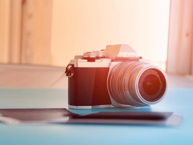 木製のテーブルの上の古いカメラのレンズの写真を閉じます。画像はレトロフィルター処理されています。