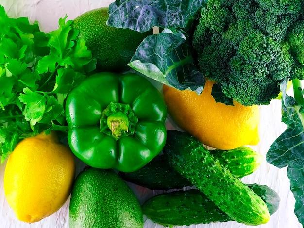 グリーントーンの盛り合わせ野菜、新鮮な有機原料、木製のテーブルに新鮮な緑野菜のフラットレイアウトシリーズ